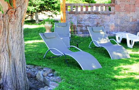 Grey fabric sun loungers in green summer garden Stock Photo