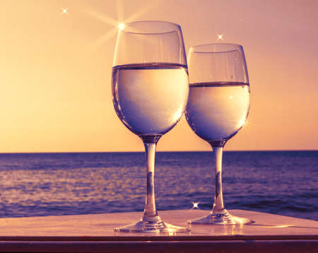 Two glasses of wine at sunset against sea horizon