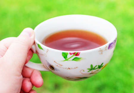 Cup of tea in hand on green summer background