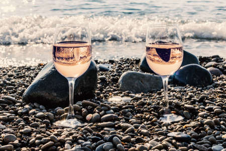Two glasses of pink wine near sea at sunny morning