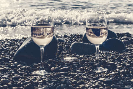 Two beauty glasses of white wine by sea