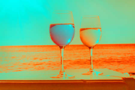 Two glasses by sea in fancy blue and orange colors Stock Photo