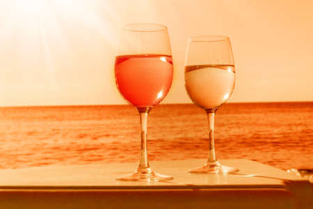 Two glasses by sea in orange for happy mood Stock Photo
