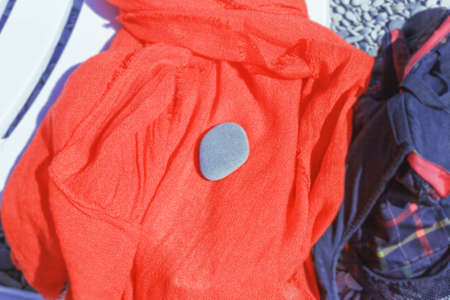 One gray pebble on orange scarf on sunbed at sunny day