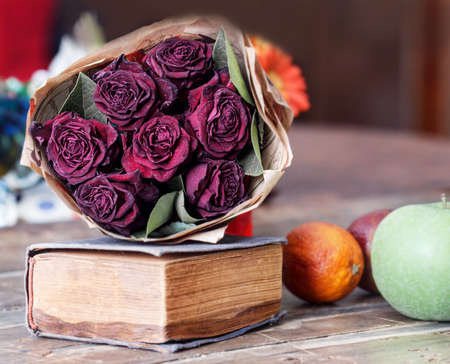 Still life with dry red roses and old book with fruits Stock Photo