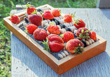 Fresh red ripe strawberries on old accounts at summer day