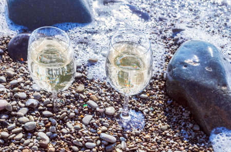 Two glasses of white wine by sea at morning