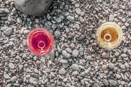 Two charming glasses of white and red wine on sea pebbles