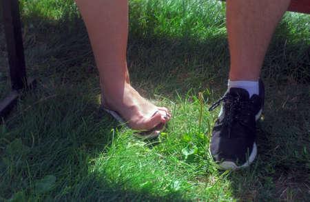 Womens and mens leg on green sunny summer grass