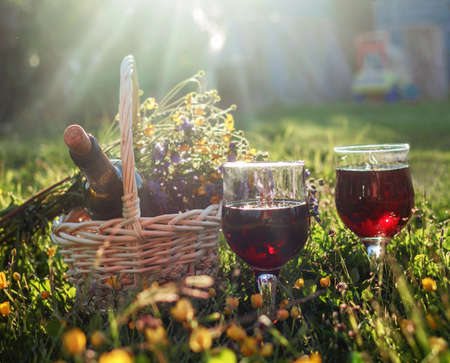 Red wine in glasses in happy sunny meadow Stock Photo