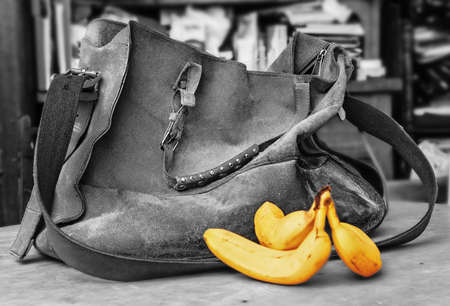Old suede bag and three ripe bananas in black ans white Stock Photo - 115113356