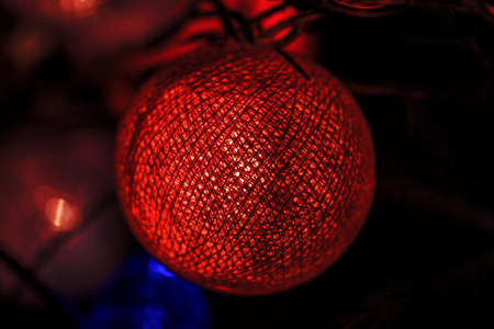 Orange glowing ball of threads on Christmas tree in dark Stock Photo - 114741957