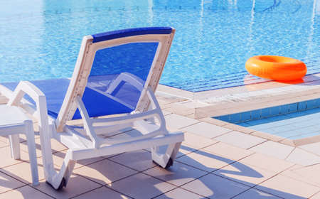White blue sunbed by pool with light blue water at sunny day Stock Photo