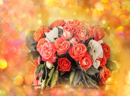 Pretty bouquet of red and pink roses on bright gold holiday light background