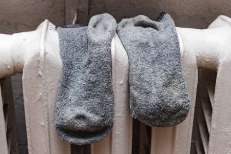 Old grey socks to dry on battery in room at day