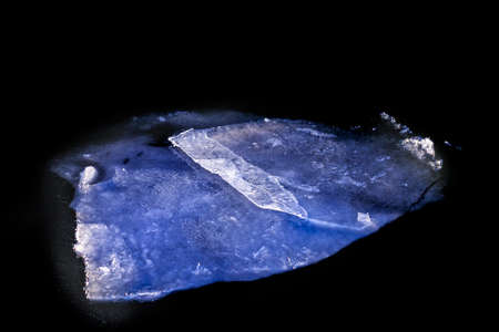 Big mystic magnificent ice floe in dark water at winter weather