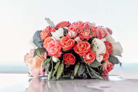Pretty bouquet of red and pink roses on light background