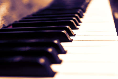 Close up piano keys black and white in light red sepia