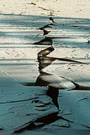 Original geometric crack in ice at winter day