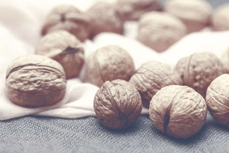 Pretty walnuts large on pink and gray background in sepia