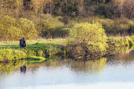 Fisherman at spring river sunny green evening Stock Photo
