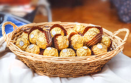 Ferrero Rocher chocolates in wooden basket for editorial use 写真素材