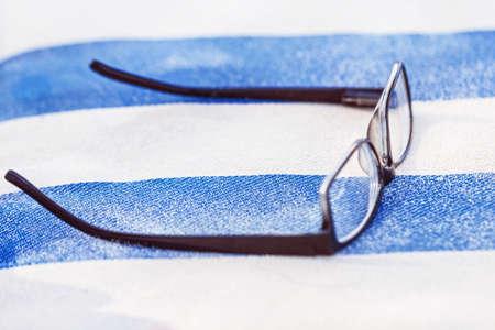 Black glasses on beach mattress at day