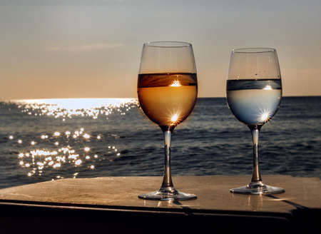 Two glasses of wine at sunset by sunny rays sea