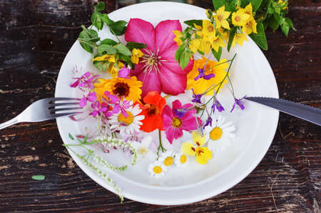 Multicolour flowers in plate fork and knife Stock Photo