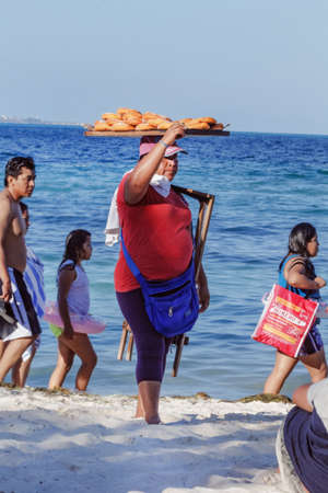 Cancun, Mexico - March, 17, 2019: bakery saleswoman on beach at sunny day in Cancun beach Editorial