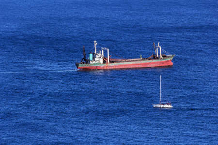 Cargo barge and small yacht on blue sea at day