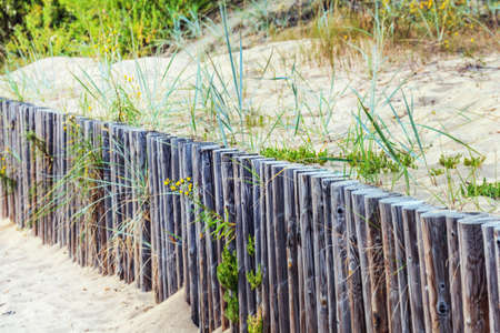 Wooden fence in dunes at summer day Stock Photo