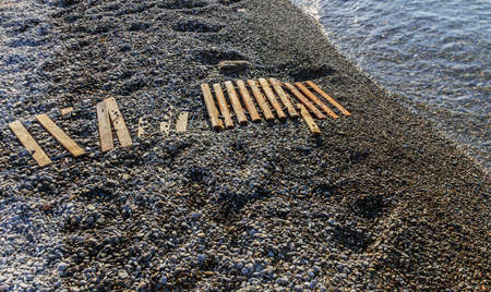 Real wooden path on stones pebbles to sea at sunny morning