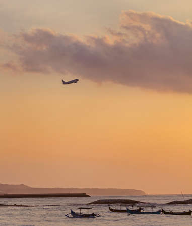 Boats in sea, plane in ocean at sunset