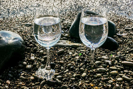 Two pretty glasses of water on sea pebbles by water