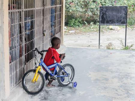 Nungwi, Zanzibar, March 18, 2020: pretty dark skinned boy with bicycle at day