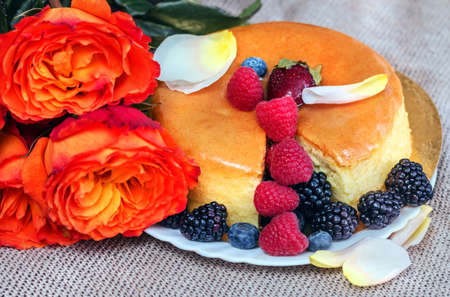 Orange roses, fresh ripe berries and tasty pie for holiday