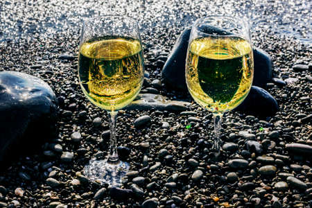 Two glasses of white wine on pebbles seashore at sunny morning