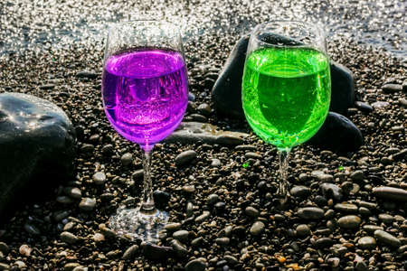 Two glasses of lilla and green drinks on pebbles seashore at sunny morning