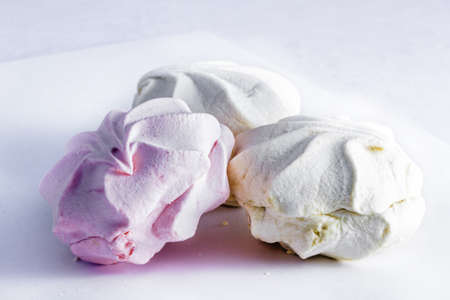 Three marshmallows, pink and white, on gray background