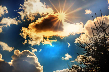 Sun rays and clouds in big blue sky