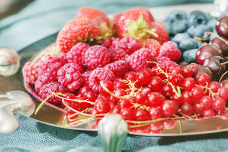 Pretty multicolor ripe fresh berries on platter for tasty eating Standard-Bild