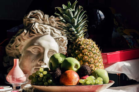Real still life with fruit and plaster head of Apollo