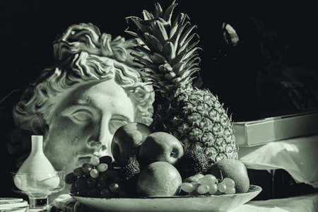 Real still life with fruit and plaster head of Apollo in sepia Standard-Bild