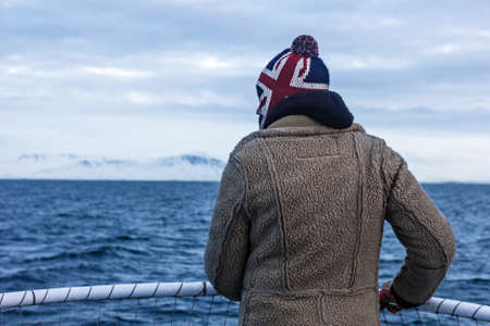 January, 3, 2016 - Atlantic ocean ship, Iceland; Real man looks into distance at snow-capped mountains and cold sea