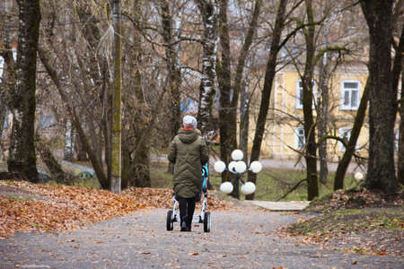 Woman walks with baby stroller on gloomy autumn day