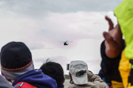 Russian real military helicopter in sky through eyes of people in crowd