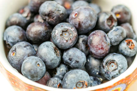 Raw tasty blueberries in colorful bowl for cozy delicious snack Stock Photo