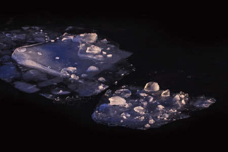 Real beautiful winter pieces of ice in deep dark water
