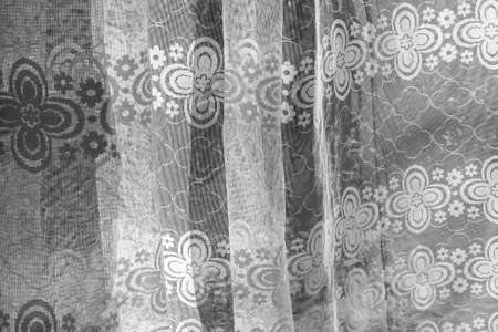 Real curtain made of white tulle with patterns in black and white